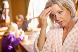 Caucasian blonde mom  in foreground in bathrobe holding head in frustration, while kids fight in background in kitchen.