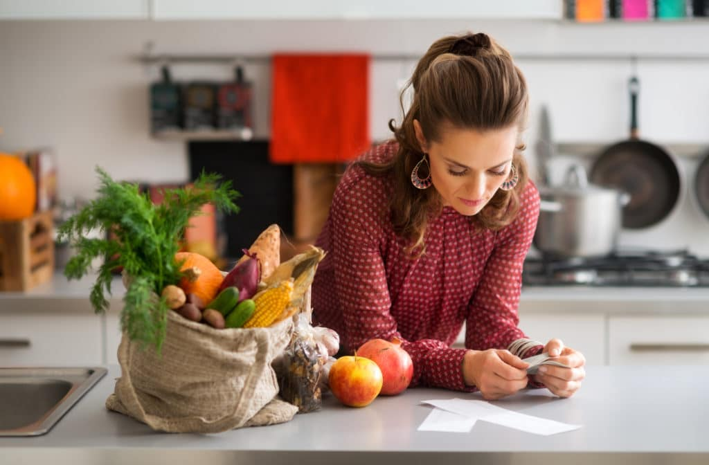 Woman in kitchen reading shopping list
